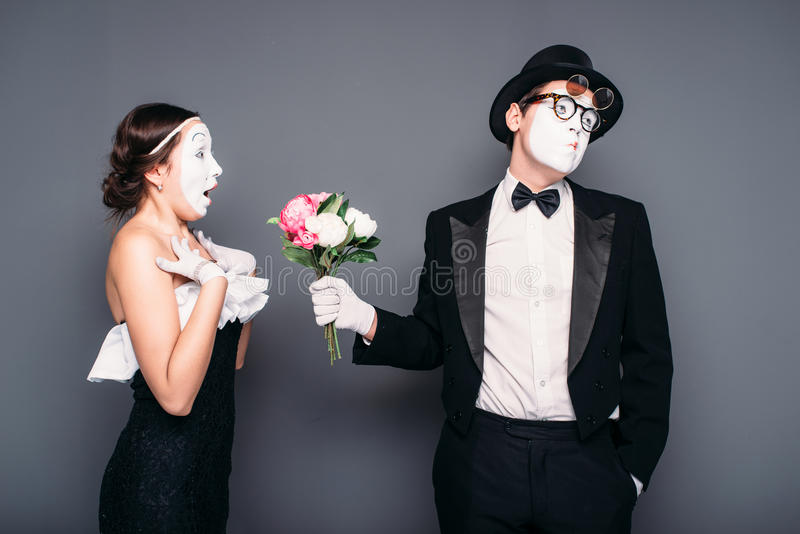 Pantomime actors performing with flower bouquet. Pantomime actor and actress performing with flower bouquet. Mime theater performers posing. Comedy artists royalty free stock photos