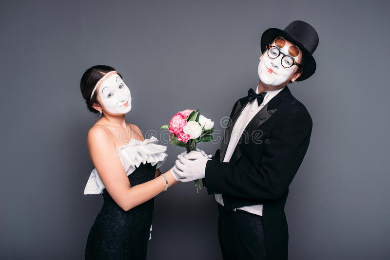 Pantomime actors performing with flower bouquet. Pantomime actor and actress performing with flower bouquet. Mime theater performers posing. Comedy artists royalty free stock photo