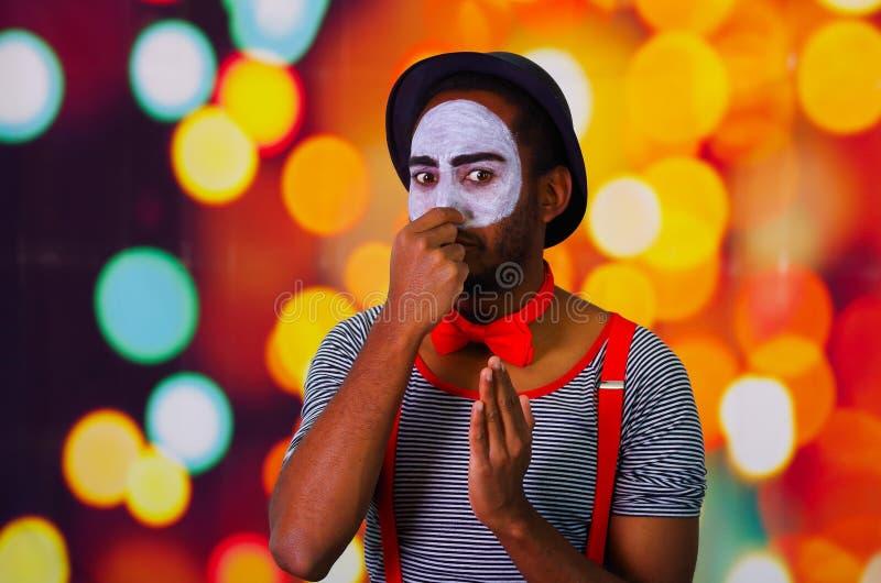 Pantomime al hombre que lleva la pintura facial que presenta para la cámara, usando lenguaje corporal que obra recíprocamente de  fotografía de archivo