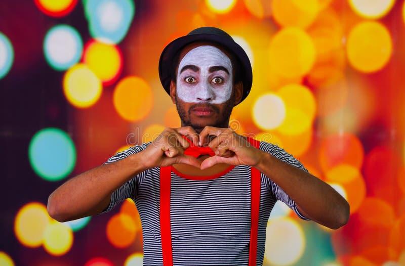 Pantomime al hombre que lleva la pintura facial que presenta para la cámara, usando lenguaje corporal que obra recíprocamente de  fotos de archivo