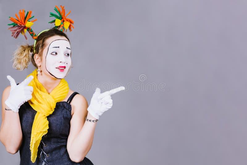 Pantomime de fille posant près d'un fond gris photographie stock