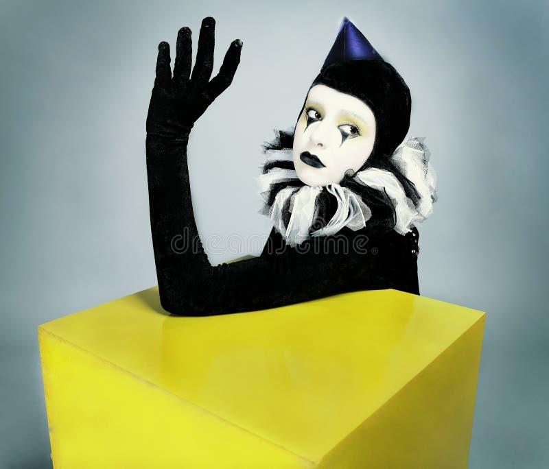 Pantomime de mode de cirque posant près d'un grand dos jaune image stock