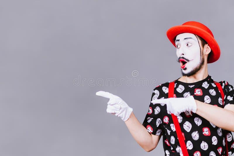 Pantomime drôle posant près d'un fond gris photo libre de droits