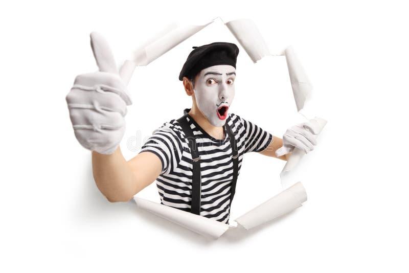 Pantomime enthousiaste regardant par un trou de papier criqué et montrant des pouces  photo libre de droits