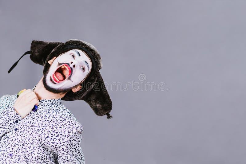 Pantomime gai posant sur un fond gris de mur photos stock