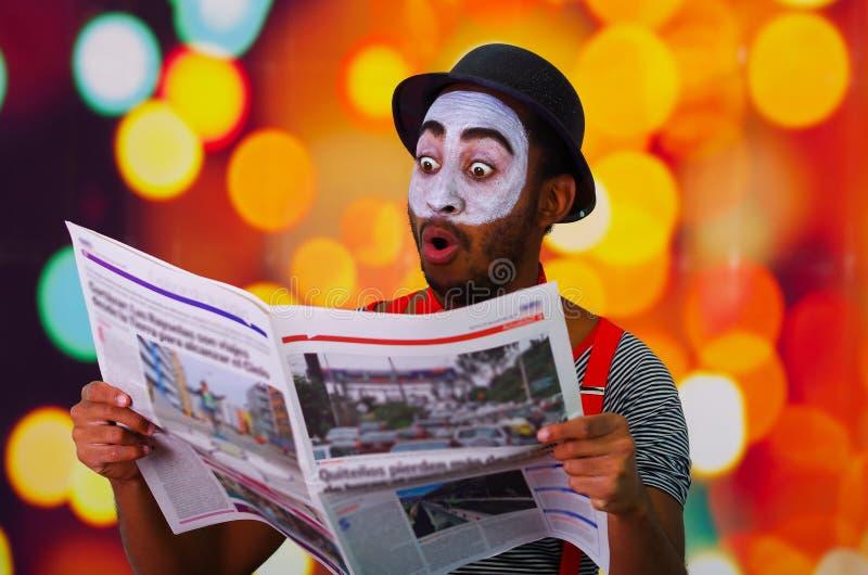 Pantomime Mann mit der Gesichtsfarbe, die für die Kamera aufwirft, welche die Zeitung hält, die lustiges Gesicht, undeutlichen Li stockfotografie