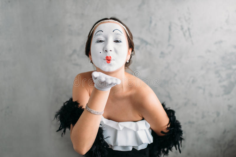 Pantomime theater actress posing in studio. Pantomime theater actress with white makeup mask posing in studio. Comedy female artist performing. April fools day royalty free stock photo