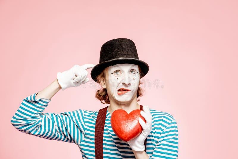 Pantomimo con cuore rosso sui precedenti rosa fotografia stock libera da diritti