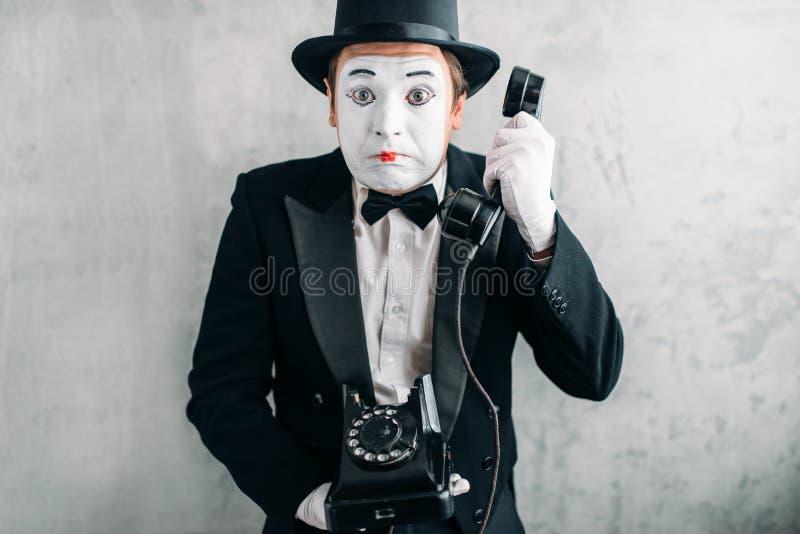 Pantomimskådespelare som utför med den retro telefonen royaltyfria bilder
