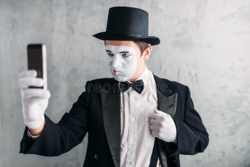 Pantomimskådespelaren med makeupmaskeringen gör selfie arkivbild