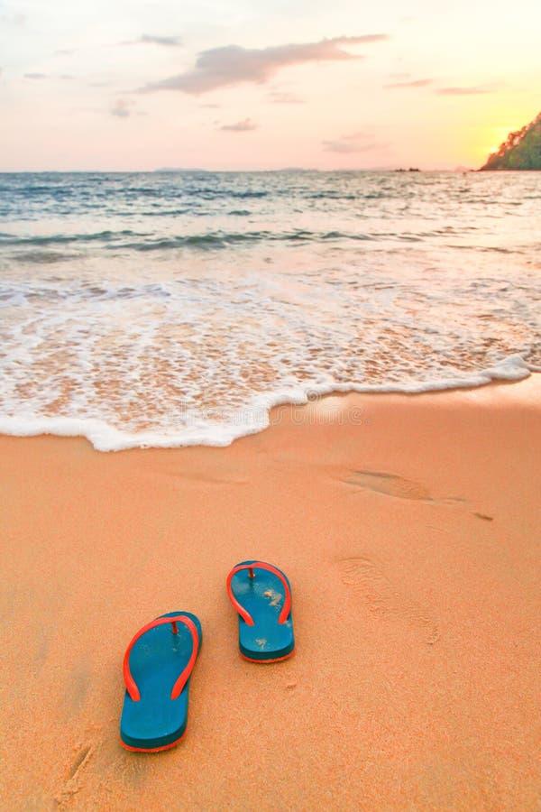 pantoufle et coucher du soleil sur la plage photos libres de droits