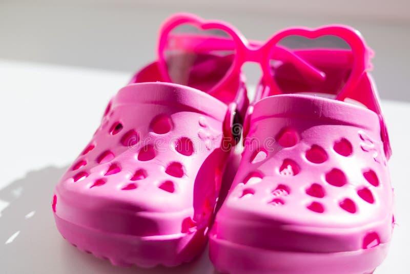 Pantoufles en caoutchouc roses, d'isolement sur le fond blanc Les sandales en caoutchouc des enfants d'isolement Chaussures confo images libres de droits