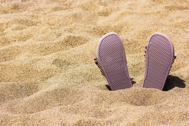 Pantoufles roses de plage dans le sable sur la plage photo libre de droits