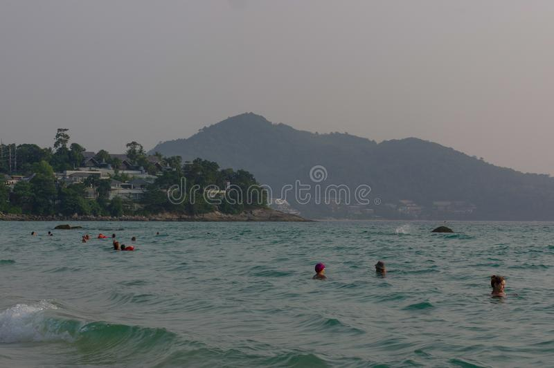 PANWA BAY AND BEACH, PHUKET ISLAND, THAILAND - MARCH 29, 2016: Beautiful landscape seaview with swiming people and boats at beach. PANWA BAY AND BEACH, PHUKET royalty free stock images