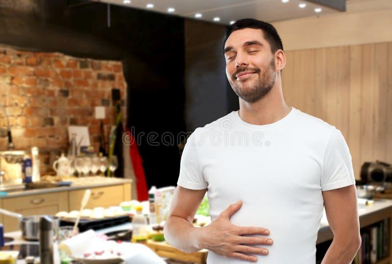 Panza conmovedora del hombre lleno feliz sobre cocina fotografía de archivo