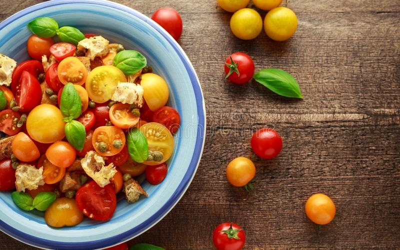 Panzanella蕃茄沙拉用红色,黄色,橙色西红柿、雀跃、蓬蒿和ciabatta油煎方型小面包片 健康的夏天 免版税库存图片