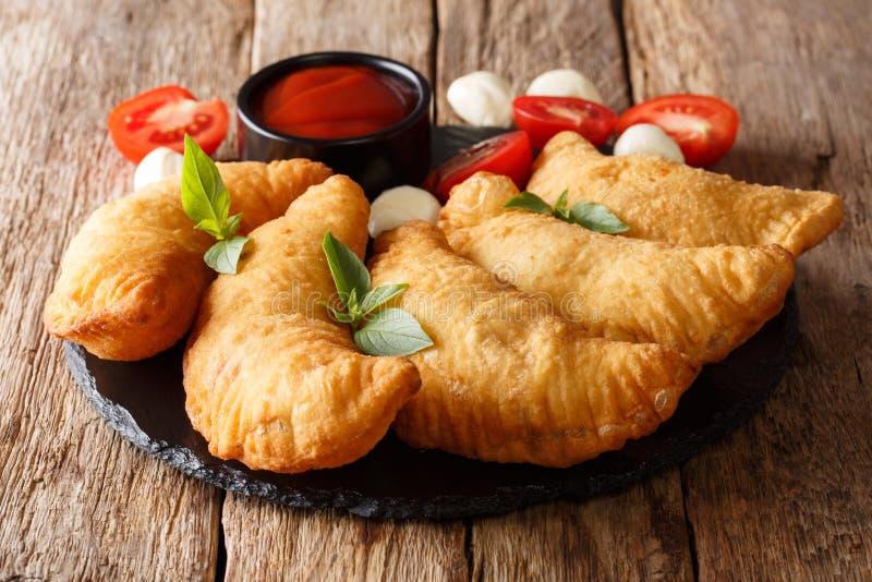 Panzerotti frit chaud avec un remplissage des tomates, des herbes et du mozza images libres de droits