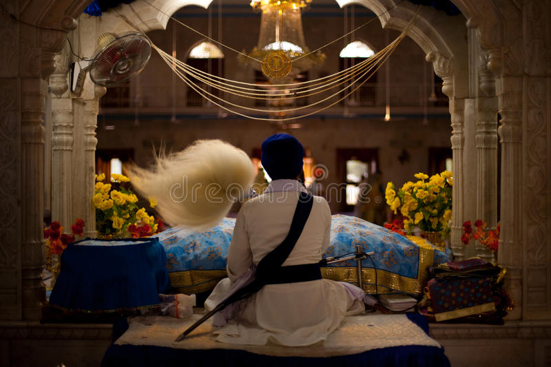 Paonta Sahib Altar Priest Sikh. Paonta Sahib - May 23: A Sikh man waves a fluffy wand at an ornately carved and decorated altar inside the Paonta Sahib gurudwara royalty free stock photo
