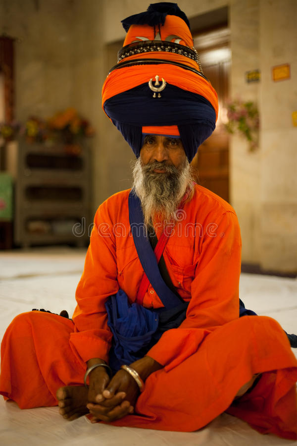 Paonta Sahib Leader Sits Saffron. PAONTA SAHIB - MAY 23: The learned elder of the Paonta Sahib gurudwara attends a service in wonderfully beautiful saffron robes stock image