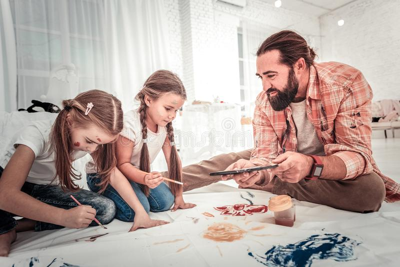 Papà allegro e figlie felici che riuniscono nella camera da letto fotografia stock