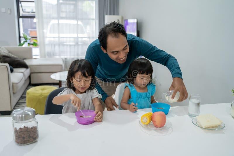 Papà asiatico che mangia prima colazione con la sua bambina due fotografia stock libera da diritti