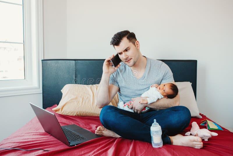 Pap? caucasico del padre con il bambino cinese asiatico neonato della corsa mista che lavora dalla casa immagini stock
