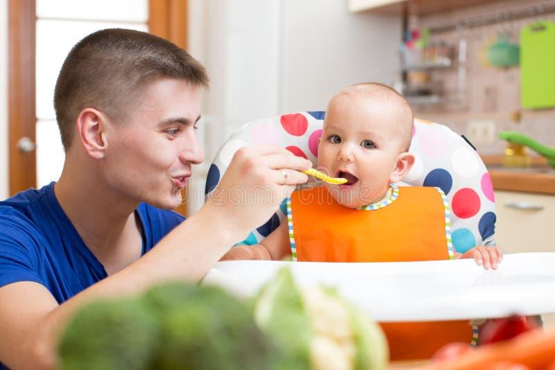 Papà che alimenta il suo bambino alla cucina fotografia stock libera da diritti