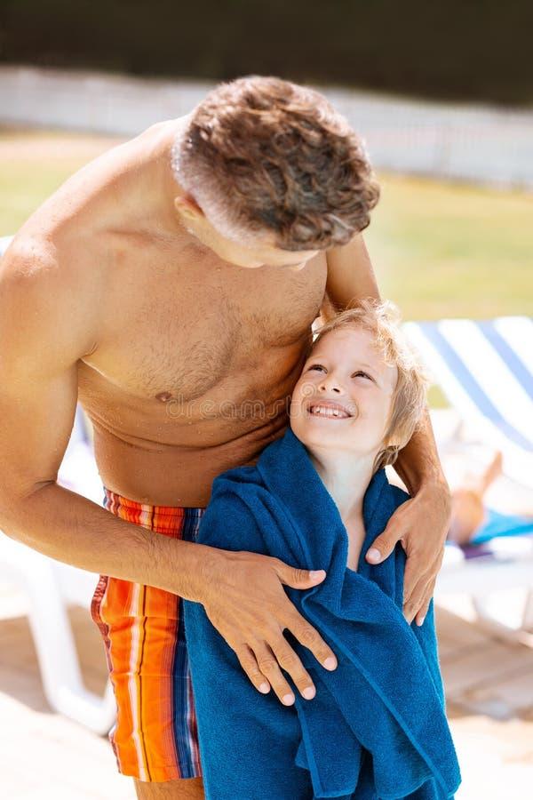 Papà che esamina la sua condizione sorridente del figlio in asciugamano fotografie stock