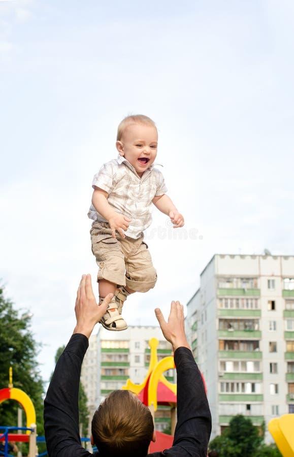 Papà che lancia suo figlio infantile su all'aperto immagine stock