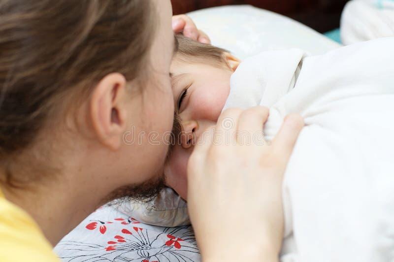 Papà che mette figlia per dormire immagine stock