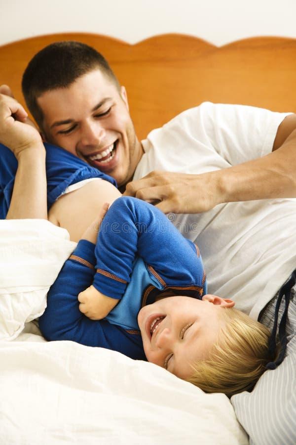 Papà che solletica bambino. fotografia stock libera da diritti