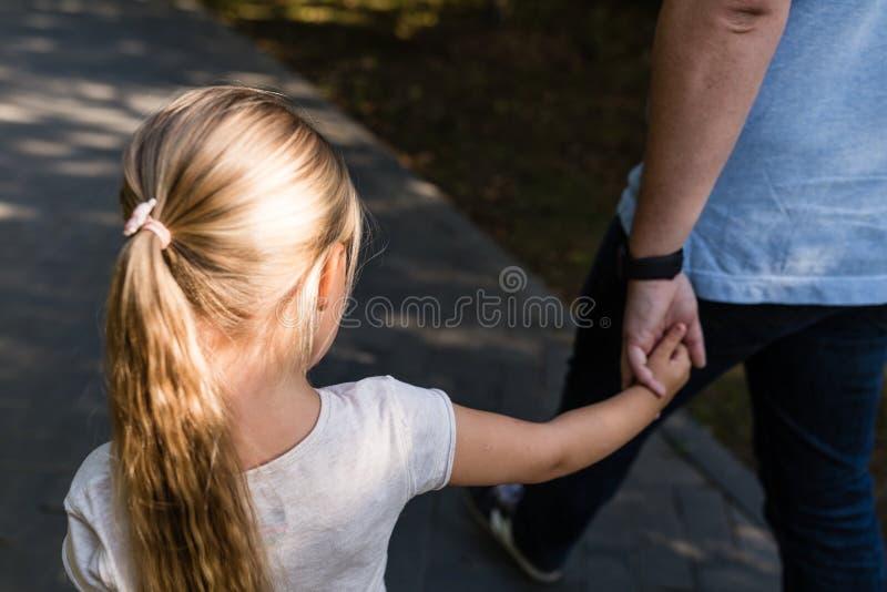 Pap? che tiene la figlia delle mani con amore e che cammina nel parco Concetto 'nucleo familiare' fotografia stock libera da diritti