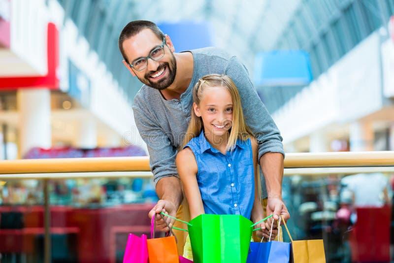 Papà con acquisto della figlia nel centro commerciale fotografie stock libere da diritti