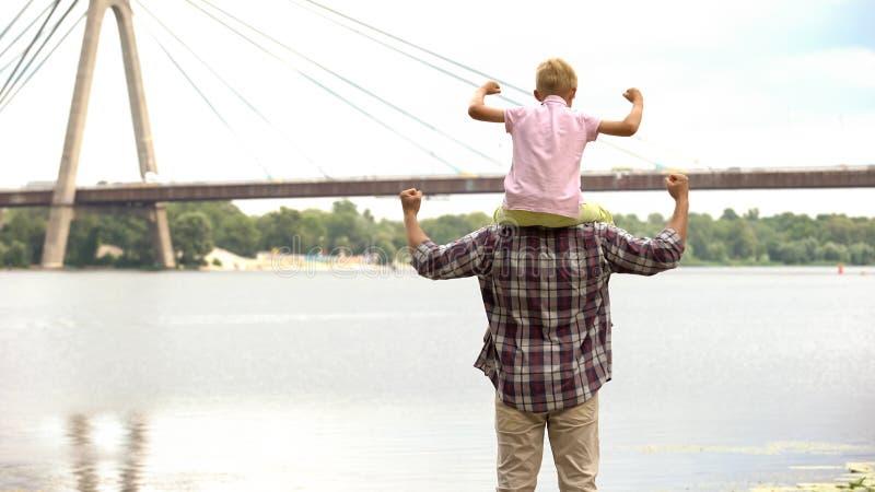 Papà con il figlio sulle sue spalle che esaminano città, mostrando forza e fiducia immagini stock libere da diritti