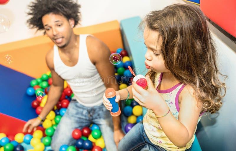 Papà dell'America latina che gioca con la figlia della corsa mista alla stanza dei giochi immagine stock libera da diritti
