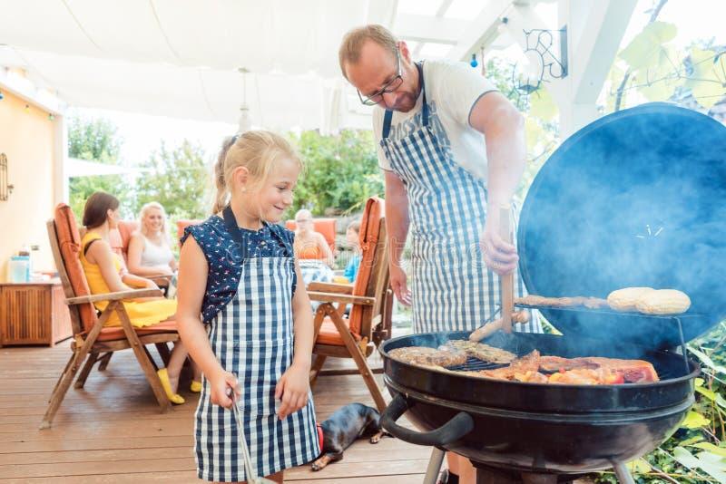 Papà e bambino che fanno il barbecue alla griglia fotografia stock