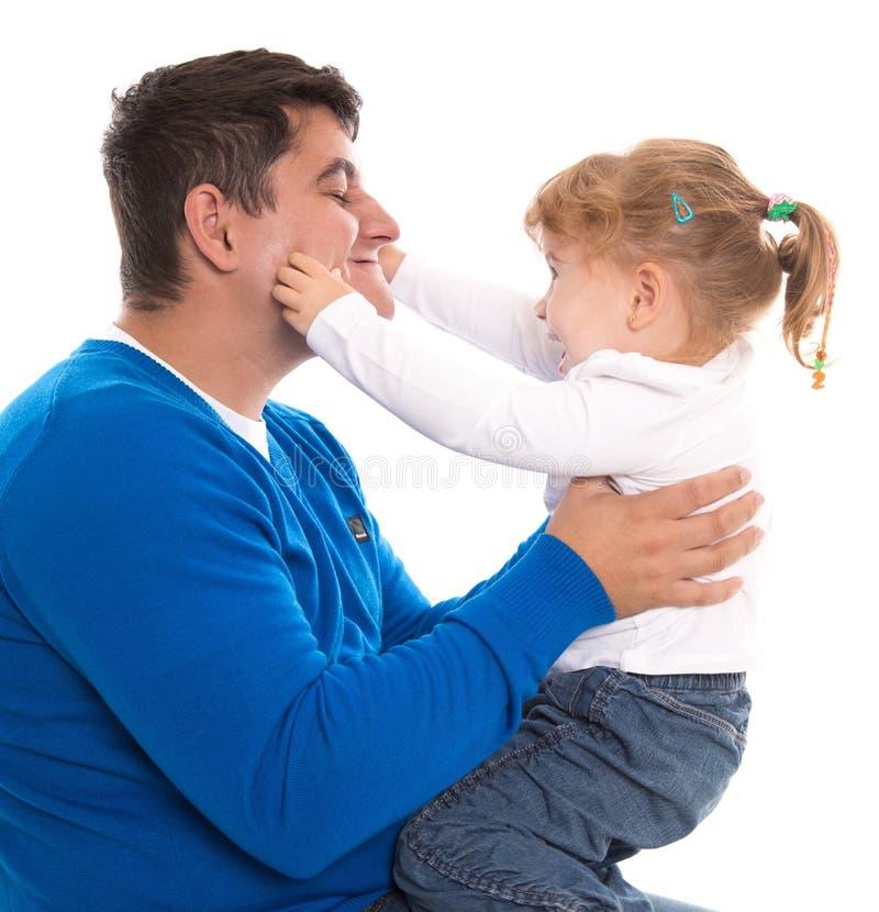 Papà e bambino che giocano e che pizzicano le guance isolate sulla parte posteriore di bianco fotografia stock