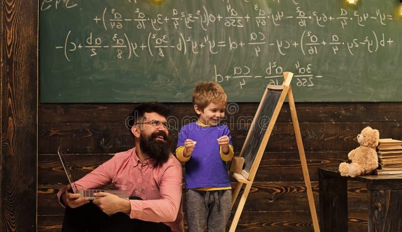 Papà e bambino che ridono mentre imparando le nuove cose Insegnante e scolaro sorridenti divertendosi insieme bambino felice alla fotografie stock libere da diritti