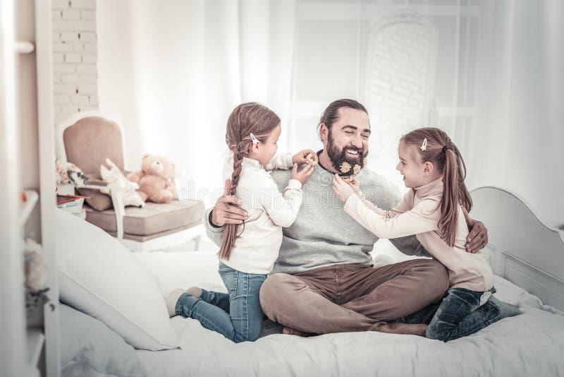 Papà e due figlie che si siedono sul letto che gioca insieme immagini stock