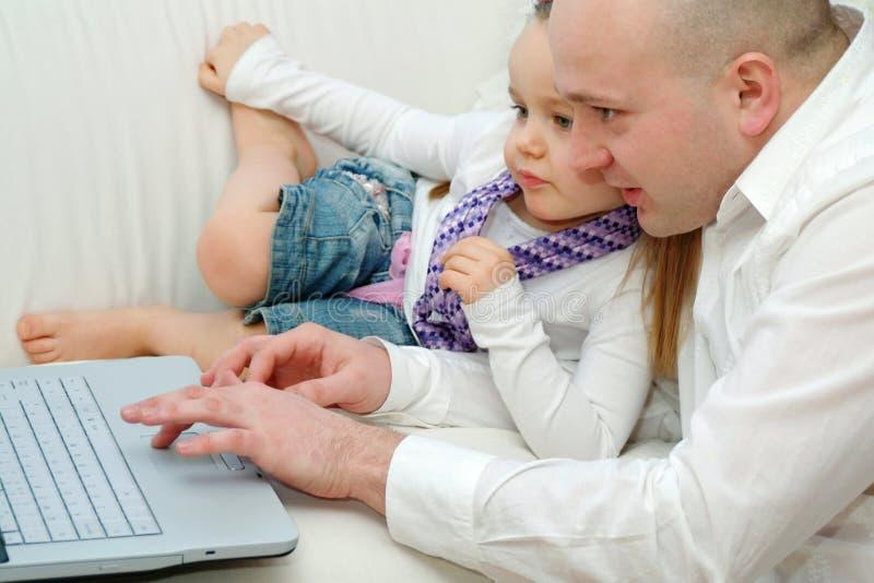 Papà e figlia con il computer portatile immagini stock