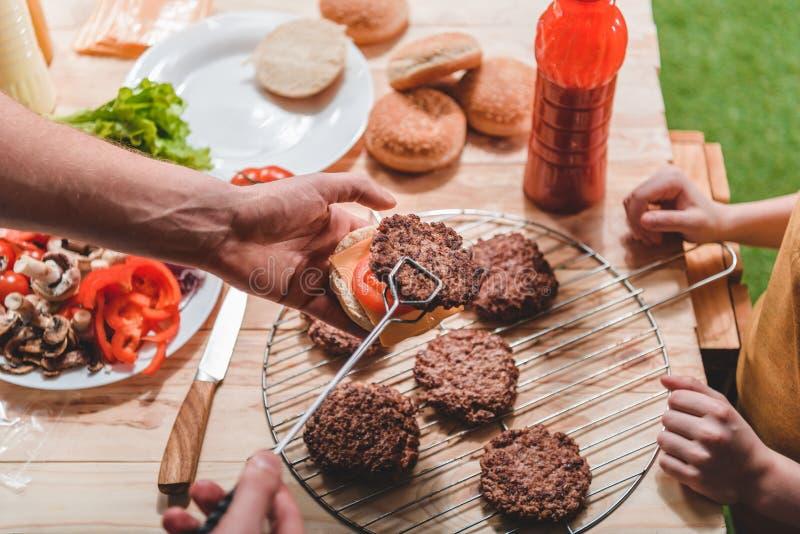 Papà e figlio che cucinano insieme gli hamburger della carne fotografia stock