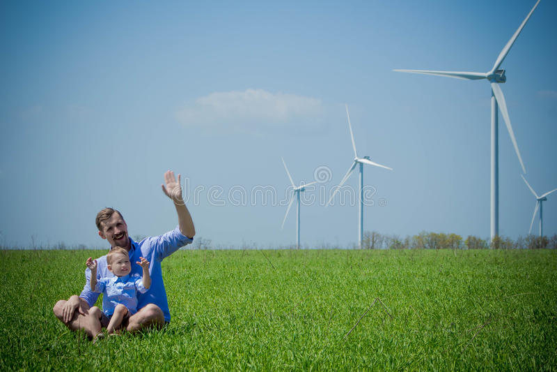 Papà e figlio che ondeggiano la loro mano ai generatori eolici fotografie stock libere da diritti