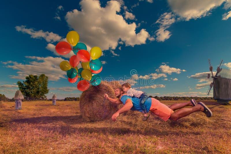 Papà e figlio che volano intorno vicino alla pila di fieno fotografia stock