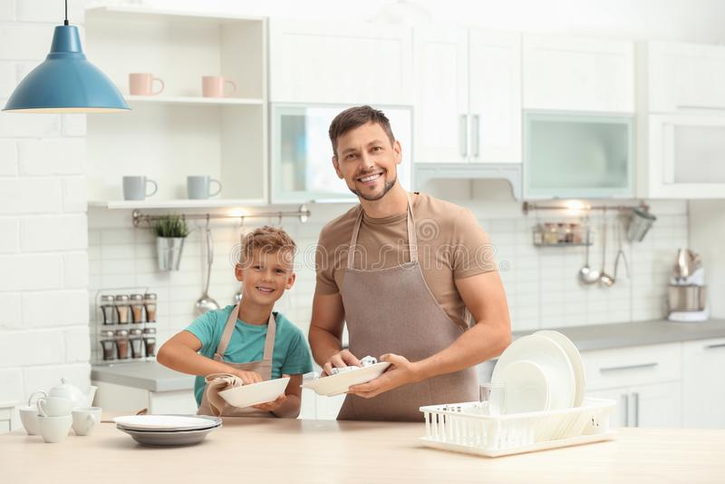 Papà e figlio lavano i piatti immagini stock libere da diritti