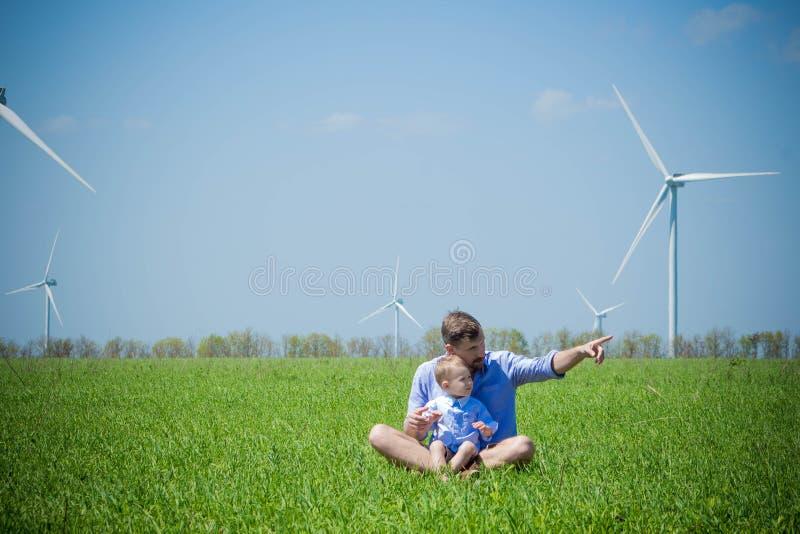 Papà e figlio sul campo con i generatori eolici fotografia stock libera da diritti