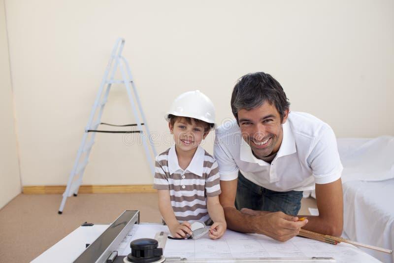 Papà e ragazzino sorridenti che studiano architettura fotografia stock libera da diritti