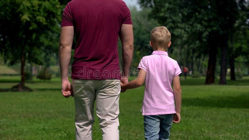 Papà e ragazzo che si tengono per mano, allontanantesi, parenting ed amicizie, famiglia felice fotografia stock