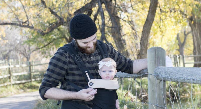 Papà millenario con il bambino nella camminata esterna del trasportatore fotografie stock