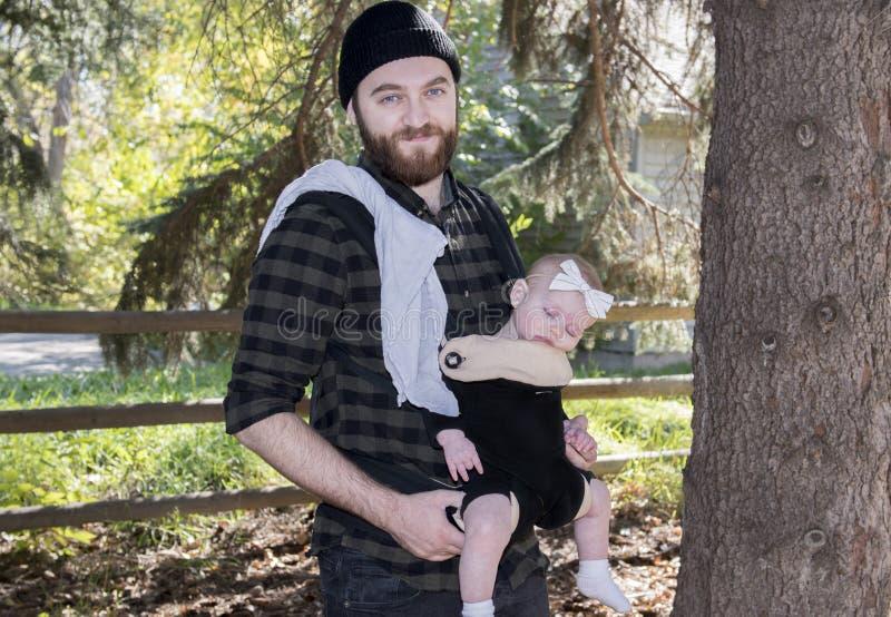 Papà millenario con il bambino nella camminata esterna del trasportatore fotografia stock libera da diritti