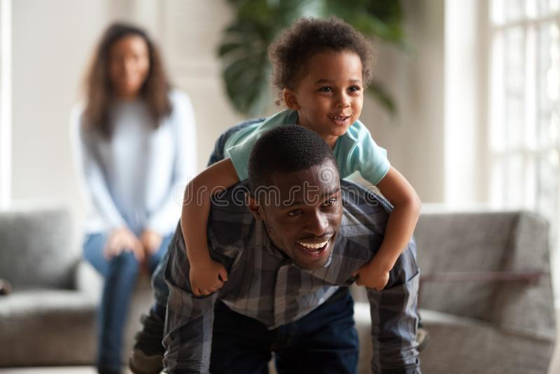 Papà nero che dà il figlio di trasporto di giro di a due vie del bambino sulla parte posteriore immagini stock libere da diritti